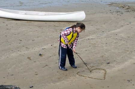 valentine s day beach: A girl is drawing a love heart on the sand Stock Photo