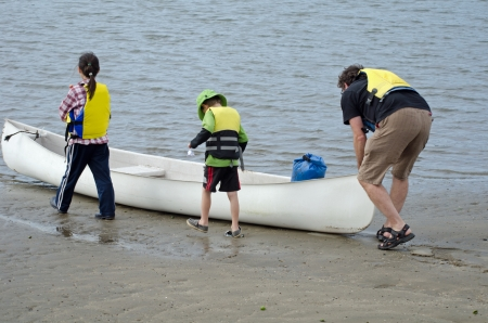 2 children and a man are getting ready for canoeing photo