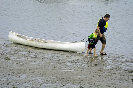 A man is dragging a canoe along the beach with a little boy