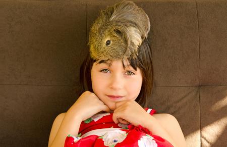 immobile: Una chica linda feliz est� sentado en el counch con un conejillo de Indias que se sienta en su cabeza Foto de archivo