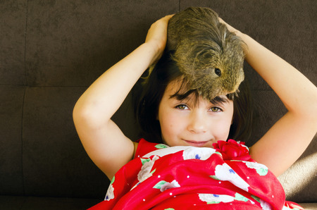 A cheeky girl with a guinea pig sitting on her head