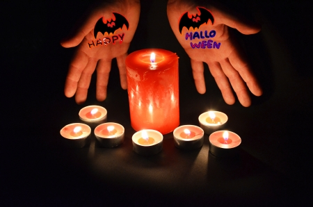 Lit candles with 2 hands spell happy halloween photo