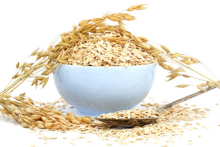 rolled oats: Rolled oats in a porcelain bowl Stock Photo