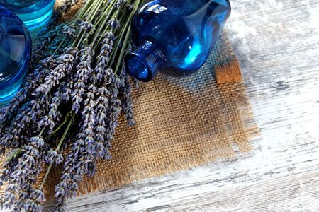 lavender oil: Lavender oil in a glass bottle on a wooden table