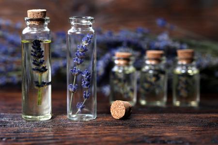El aceite de lavanda en una botella de vidrio sobre una mesa de madera