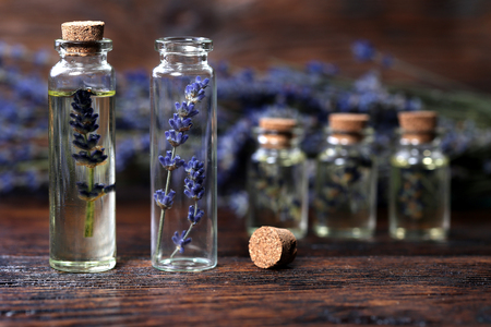 Lavender oil in a glass bottle on a wooden table