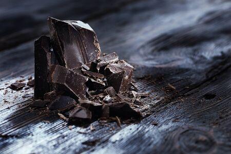 Pedazos del chocolate en una mesa de madera Foto de archivo - 54868803