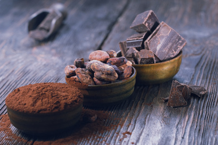 Dark chocolate pieces, cocoa powder and cocoa beans on a wooden table 스톡 콘텐츠