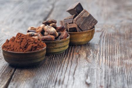 Piezas oscuras de chocolate, polvo de cacao y cacao en grano en una mesa de madera Foto de archivo - 54882584