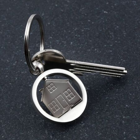annuities: Keychain figure of house and key on stone table