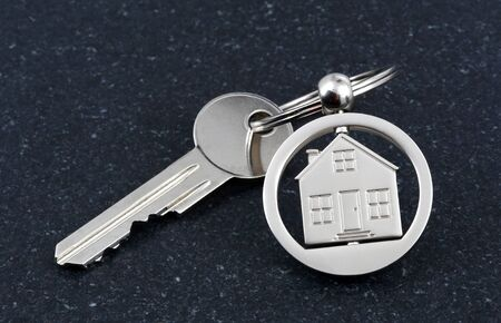 downpayment: Keychain figure of house and key on stone table