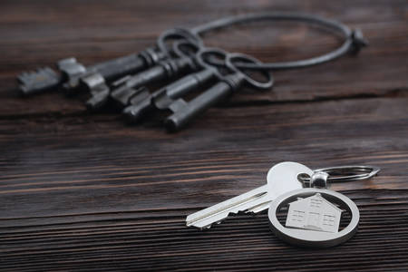 downpayment: Keychain figure of house and key on wooden table Stock Photo