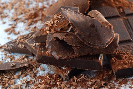 chocolate shavings: Broken dark chocolate and chocolate shavings on a wooden table