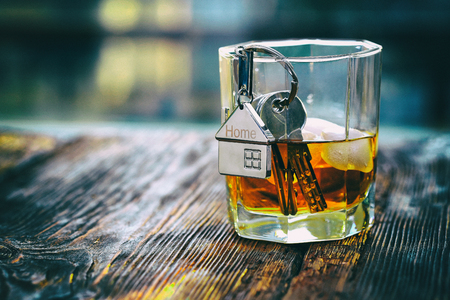 annuities: Keychain figure of house with keys and alcoholic drink Stock Photo