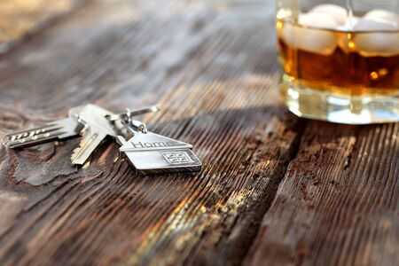 Keychain figure of house with keys and alcoholic drink Фото со стока