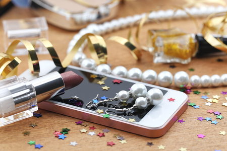 bedspread: Cosmetics, phone and jewelry on a table after party Stock Photo