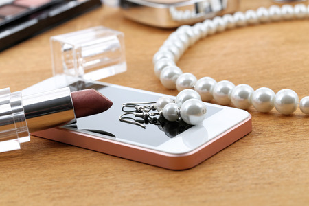 after the party: Cosmetics, phone and jewelry on a table after party Stock Photo