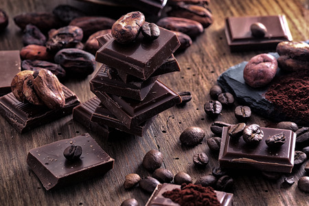 Broken dark chocolate, cocoa powder and coffee beans on a wooden table Stock Photo
