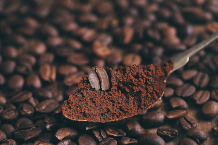 Coffee beans on a background of ground coffee Stock Photo