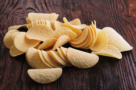 Crispy potato chips in wooden background. Salted potato chips