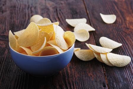 Crispy potato chips in a porcelan bowl. Salted potato chips