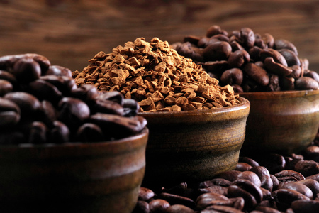 Coffee beans and coffe beans on a background of ground coffee