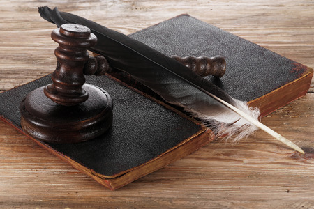 Law gavel or judge mallet and feather pen on a wooden desk