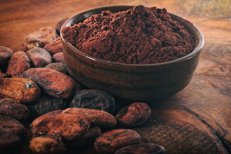 Cocoa powder and coffee beans on a wooden table