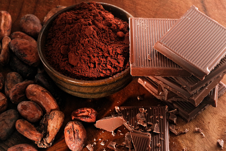 Broken dark chocolate, cocoa powder and coffee beans on a wooden table Reklamní fotografie - 117337436