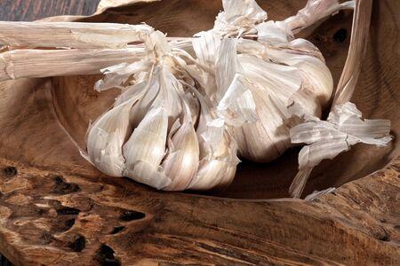 Fresh garlic bulb and garlic cloves on the wooden table Foto de archivo - 130857112