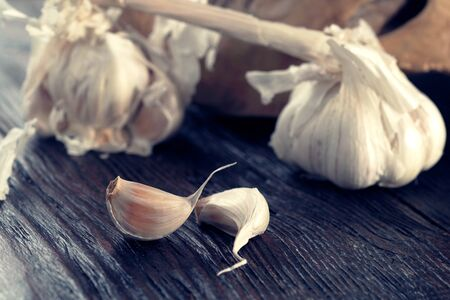 Fresh garlic bulb and garlic cloves on the wooden table Foto de archivo - 130857114