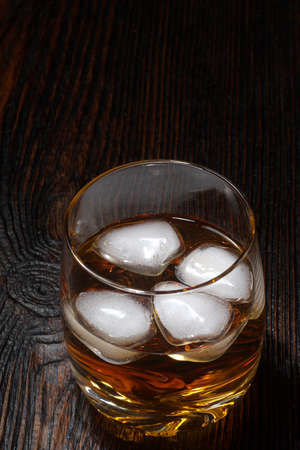 Glass of whiskey with white ice on a wooden table