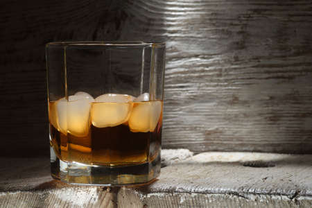 Glass of whiskey with white ice on a white wooden table