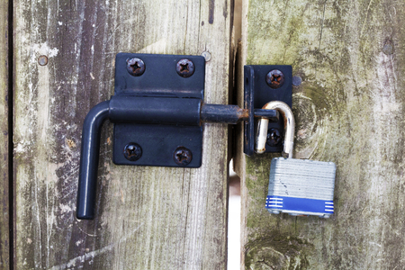 Open pad lock on closed wooden gate with black metal latch