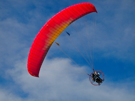 paraglide: A Paraglider flies in the blue sky Stock Photo