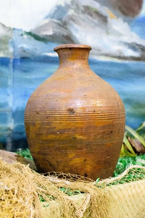 Old earthenware brown jug with a pattern. On the table. Stock Photo