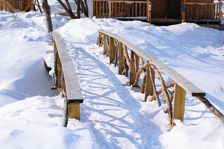 Beautiful wooden bridge from cedar across the river on a sunny winter day. In the village