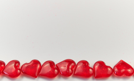 horizontal line of small red glass hearts on a white background. Valentine's Day. love symbol. copy space. greeting card Stock fotó