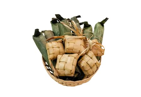 Popular Malay traditional food, Ketupat rice and Lontong Nasi Impit in one basket. Ketupats, a natural rice casing made from young coconut leaves for cooking rice on a white background.