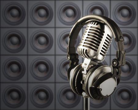 audifonos dj: Profesional 'retro' micr�fono y auriculares DJ en Spotlight contra la pared de oradores  Foto de archivo
