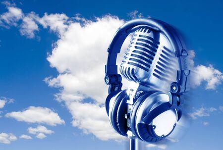 Flying Retro Microphone & Headphones Over Blue Sky Stock Photo