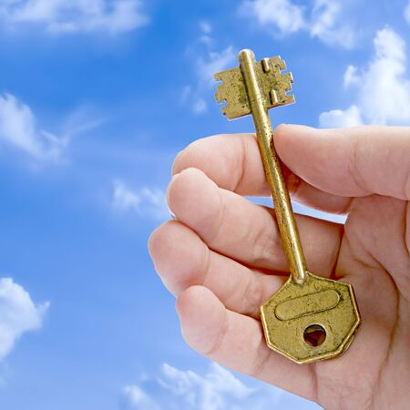Key To Success (Golden Key In A Hand Against Blue Sky)