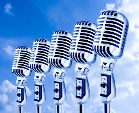 Lotta mics. Row Of Retro Microphones Against Sky photo