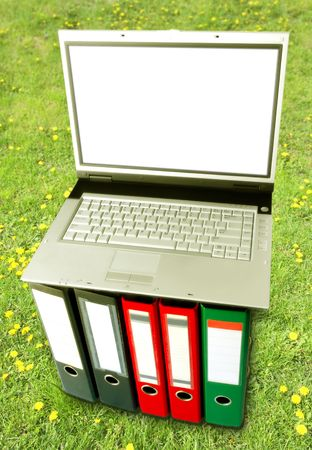 Mobile Office (Laptop On Binders Over Green Grass Background) photo