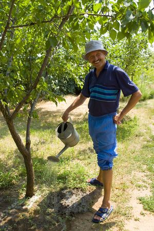 Smiling Man Watering His Orchard