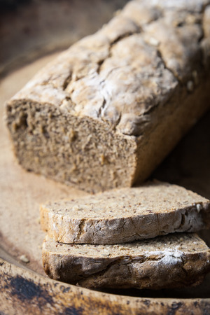 farina: Homemade wholegrain bread on a rustic wooden tray