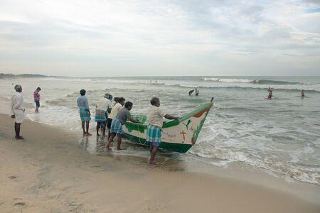 tamil nadu: Indian fishermen with boat at the coast. Mahabalipuram, Tamil Nadu, India. 2015-08-27 Editorial