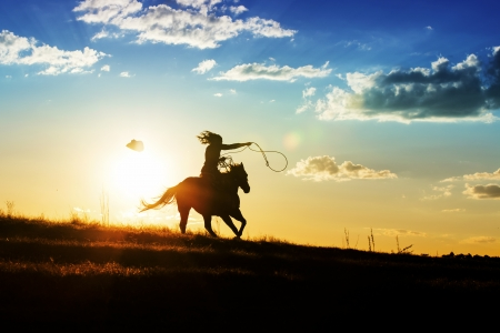 Girl loses hat while riding horse at sunset Stock Photo