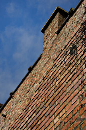 Angle shot of old brick building with blue sky background  photo