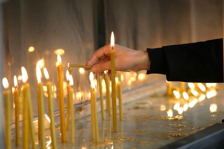 woman hand lighting candles  in a church photo